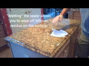 Man Showing the Ease of Cleaning a Sealed Stone Countertop