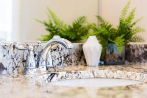 Closeup of modern bathroom sink with neutral granite countertop and mirror, green plant in pot