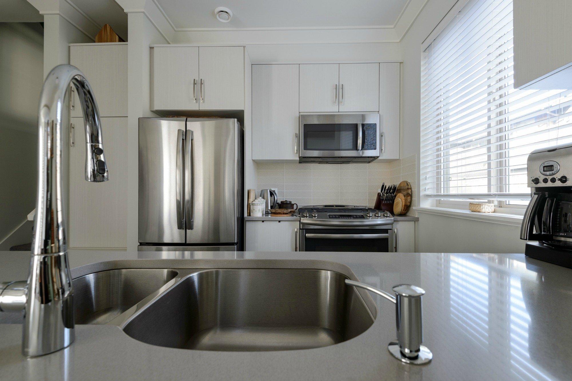 Modern white kitchen with stainless steel appliances ...