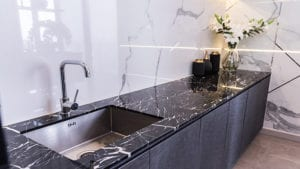 Black kitchen sink and Tap water in the kitchen. The interior of